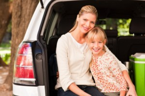 Beautiful woman with a young girl sitting in back of van, smiling